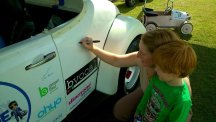 William Powell and his mother Michelle Emerson sign the Volkswagen Beetle as part of the Sign My Ride campaign