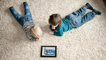 Two children watching a tablet on the floor P