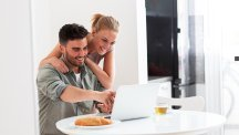 Couple in kitchen looking at laptop