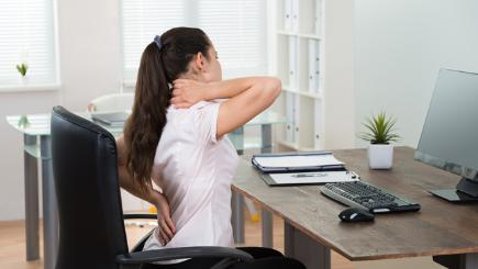 Woman at computer rubbing back