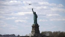 An NYPD helicopter flies over the Statue of Liberty in New York (AP)