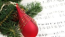 Stock image of a Christmas bauble alongside some sheet music.
