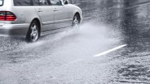 Stock image of car driving through heavy rain.