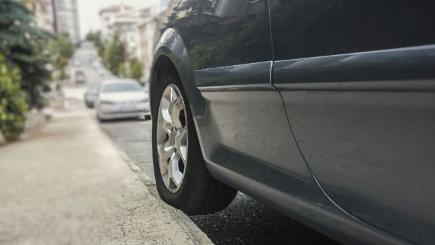 Stock image of car parked with one wheel on kerb