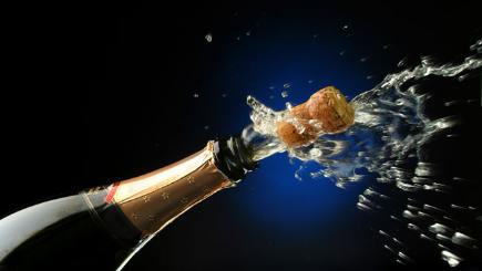 Stock image of champagne bottle cork being popped.