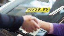 Stock image of hands being shaken over car sale.