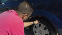 Stock image of man checking tread depth on his car tyres.