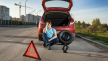 Stock image of man looking depressed at not being able to change his tyre.