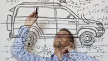 Stock image of man working on a drawn design of a car.