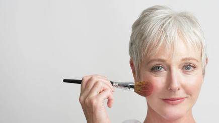 Stock image of mature woman applying make up.