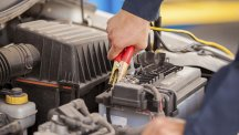 Stock image of motorist using jump leads on his car battery.