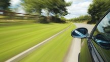 Stock image of wing mirror on car moving at speed