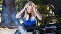 Stock image of woman looking upset as her car engine smokes.