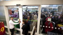 Staff hold the doors closed to an Asda store in north London closed as eager shoppers crowd to take advantage of Black Friday offers