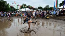 Woman splashing in mud at Glastonbury