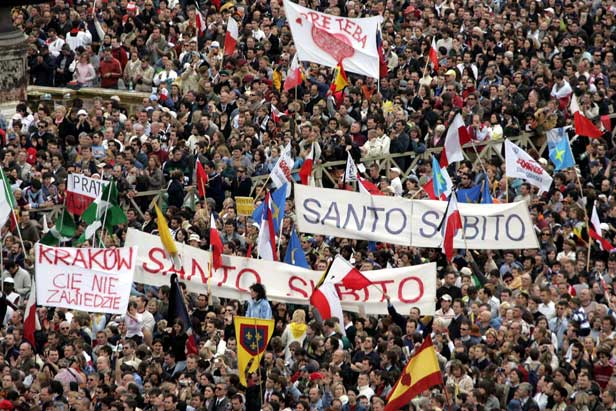 Banners in St Peter's Square read 'Santo subito' - 'Sainthood now'.