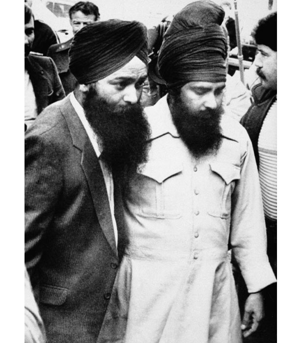 Inderjit Singh Reyat, left, and Talvinder Singh Parmar, two Sikhs charged with explosives violations in connection with the crash are escorted to court in Duncan, British Columbia, Canada.