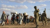 Turkish soldiers stand guard as Syrian refugees gather at the border in Suruc, Turkey (AP)