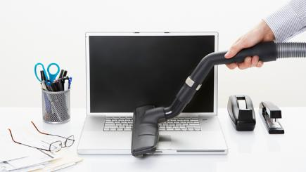 Laptop being cleaned with vacuum cleaner