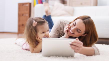 Mum sitting with daughter using tablet on carpet