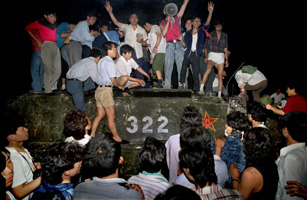 Civilians with rocks stand on a government armored vehicle near Chang'an Boulevard in Beijing as violence escalated between pro-democracy protesters and Chinese troops.