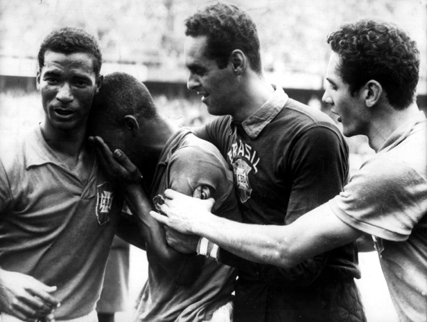 Brazil's Pele cries on the shoulder of Didi as teammates Gilmar and Orlando congratulate him on his fantastic performance in the final.
