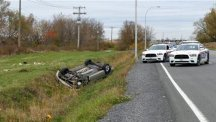 A car overturned in a ditch in a cordoned off area in St-Jean-sur-Richelieu, Quebec (AP/The Canadian Press, Pascal Marchand)