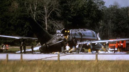 The burnt-out British Airtours jet sits on the runway at Manchester Airport