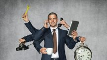 Man in grey suit with multiple hands holding clock spanner