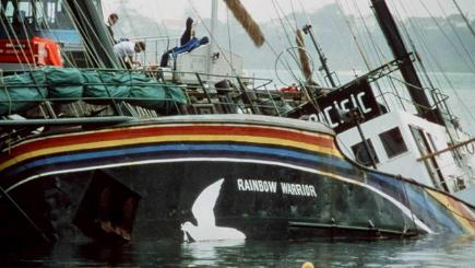The Rainbow Warrior, its hull holed, listing in Auckland Harbour.
