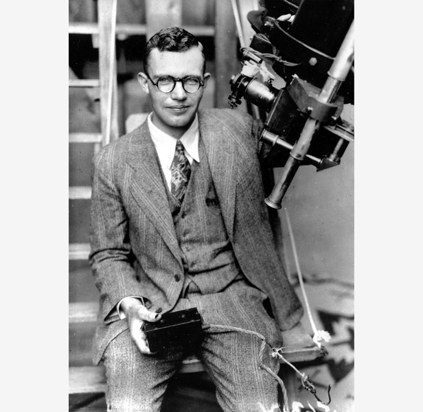 Clyde Tombaugh with the telescope through which he glimpsed Pluto in 1930.