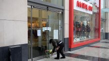 A woman leaves flowers outside the Matalan store in Queen Street, Cardiff
