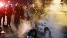 A police officer approaches a police vehicle after a protester threw a smoke device from the crowd in Ferguson (AP)