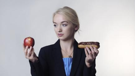 Stock image of woman holding up an apple and a chocolate eclair.