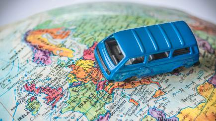 Stock image of a minivan resting on Europe as seen on a toy globe.