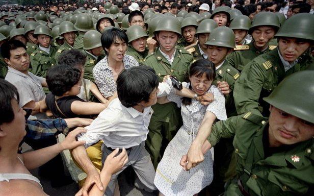 A young woman is caught between civilians and Chinese soldiers who were trying to remove her from an assembly near the Great Hall of the People.