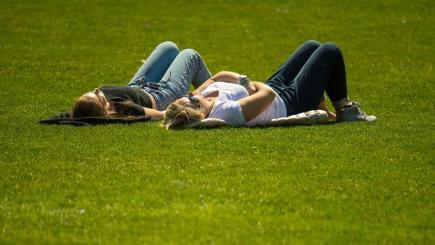 People lie in the sun in St James Park, London