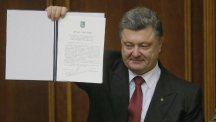 Ukrainian president Petro Poroshenko shows the Ukraine-EU Association Agreement to politicians after its signing in parliament in Kiev (AP)
