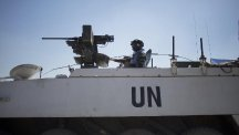 Armoured vehicles from the UN peacekeeper force wait to cross from the Israeli controlled Golan Heights to Syria (AP)