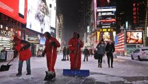Men shovel snow off a pavement in Times Square, New York City (AP)