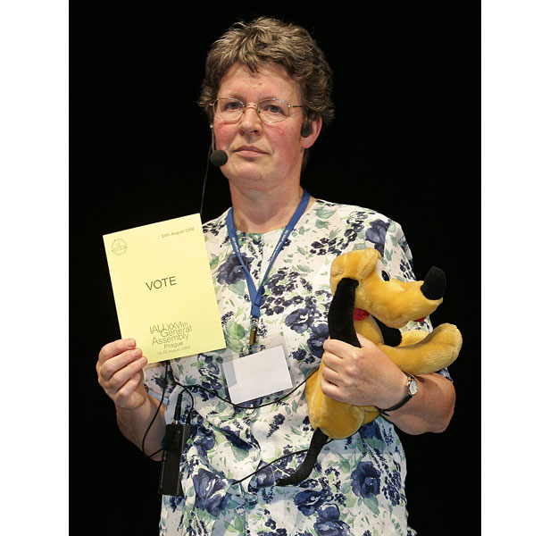 Jocelyn Bell-Burnell, member of the International Astronomical Union (IAU), with the planet's cartoon canine namesake during the vote.
