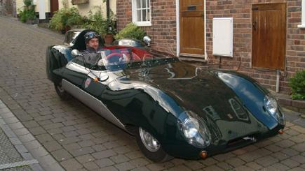 Westfield X1 kit car in British racing green with a smiling man at the wheel