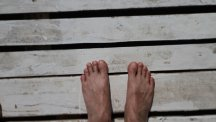 Stock image of pair of feet on a wooden pier.