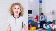 Stock image of a child shouting and an adult holding their head