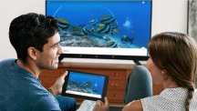 Man and woman using Chromecast on tablet and TV H