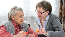 Stock image of an elderly woman and her care nurse doing a jigsaw.