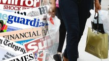 A person with shopping bags and the front pages from today's papers