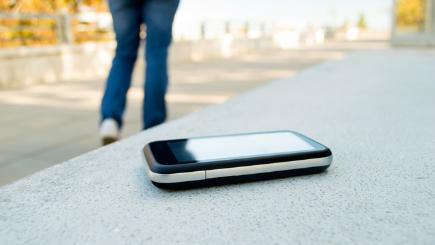 Phone left behind on bench with person walking away