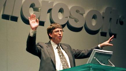 Bill Gates next to Microsoft sign