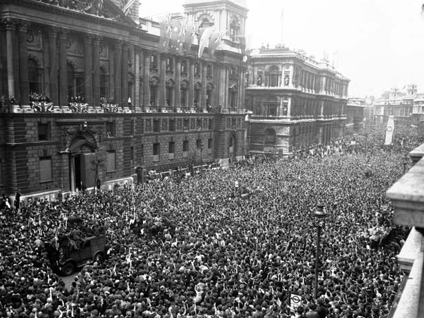 Revellers pack into Whitehall to join the celebrations and listen to Prime Minister Winston Churchill's victory speech.